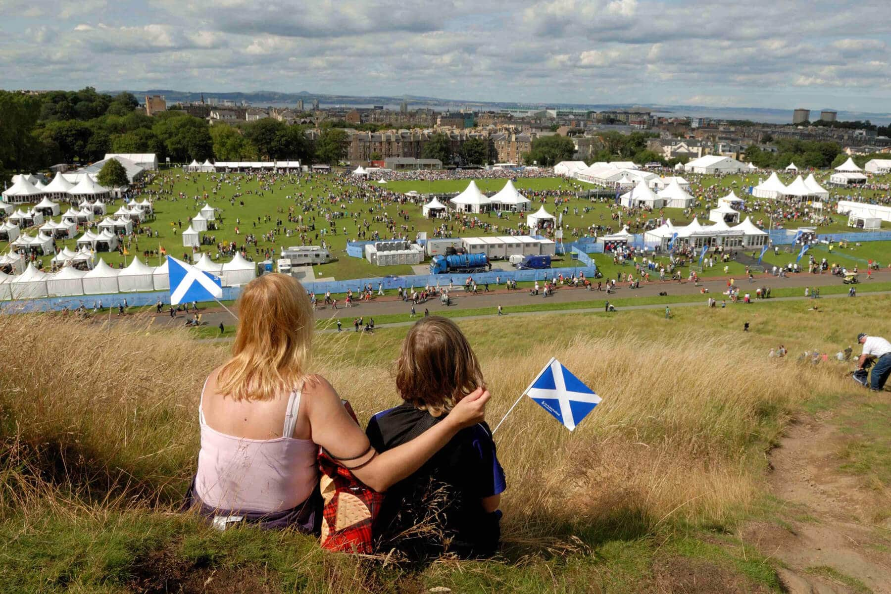 A photo of an woman and child holding small Scottish saltire flags, sitting on a hillside watching the crowds and tents of The Gathering 2009