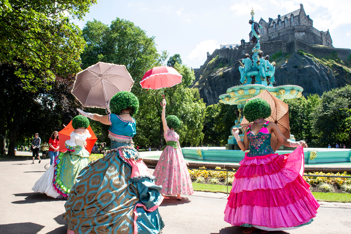 A photo of four dancers, wearing extravagant dresses and face obscuring helmets which look like bushes, in Princes Street Gardens, Edinburgh, at the launch of the newly renovated Ross Fountain