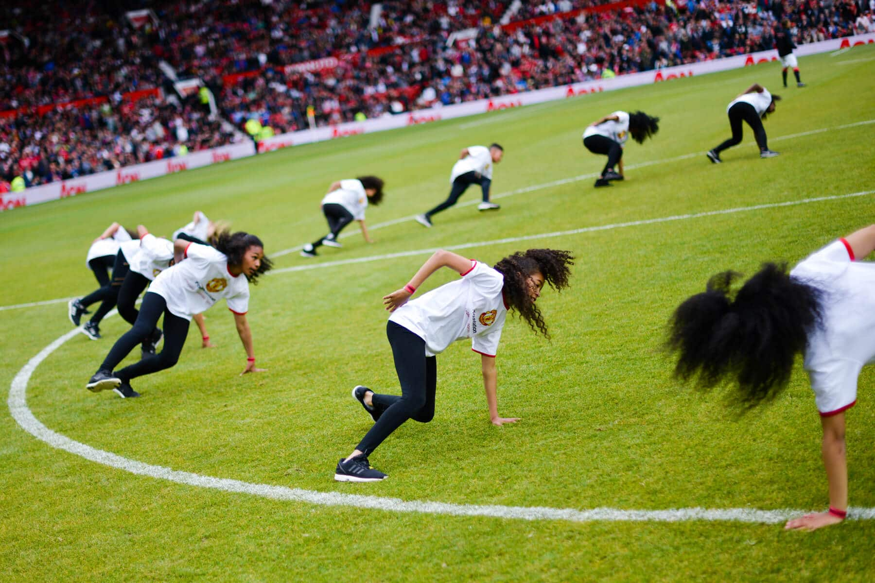 A photo of a group of children dancing in the centre circle of Old Trafford football stadium, Manchester at our Red Heart United event in 2015