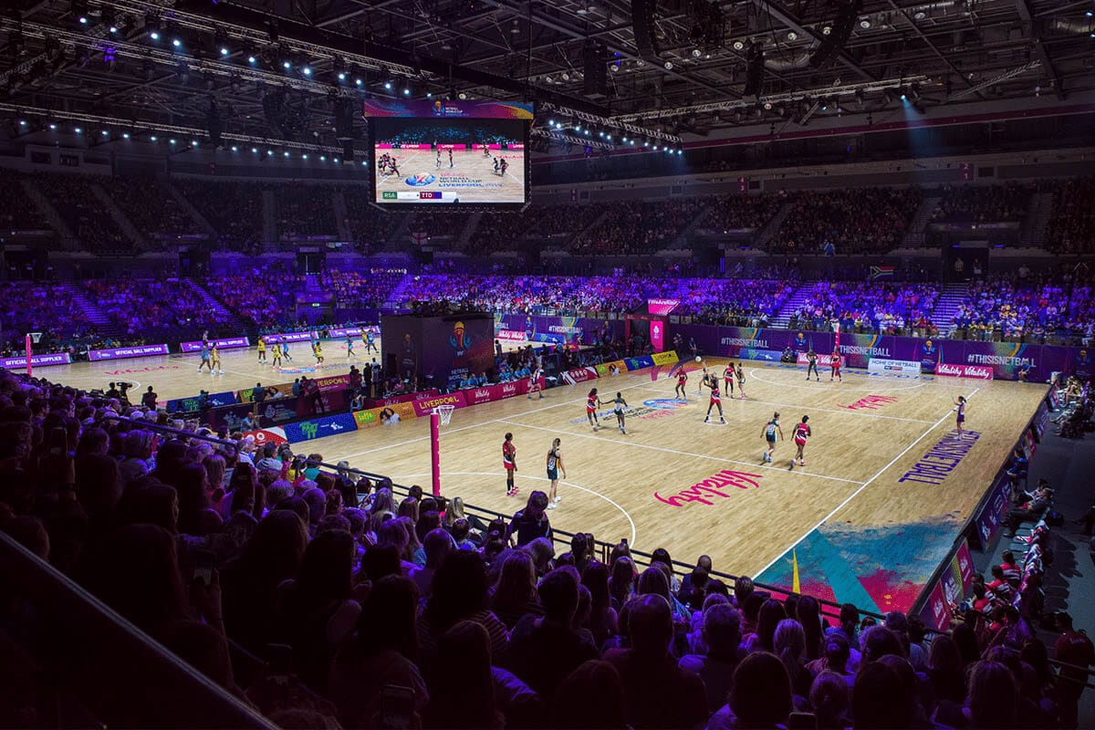 A photo of the M&S Bank Arena in Liverpool, with large crowds watching two matches take place at the Vitality Netball World Cup 2019