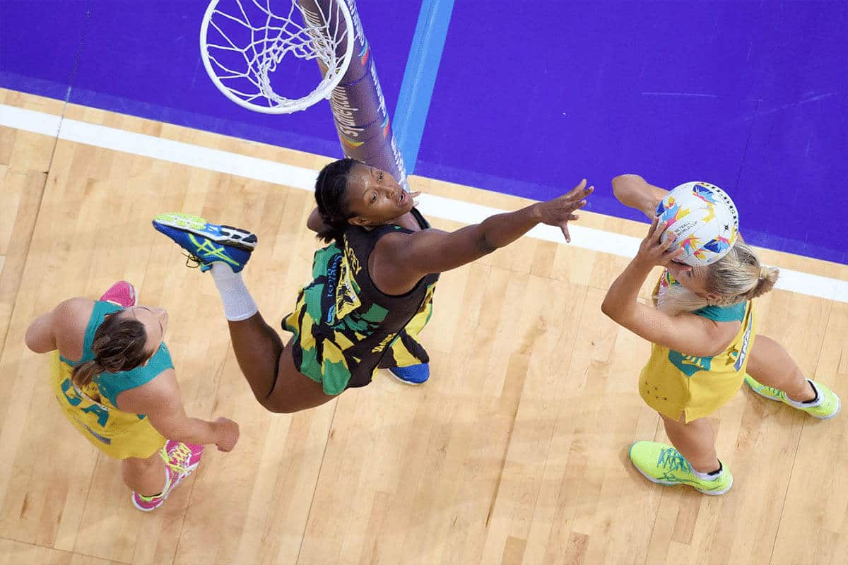 An action photo taken from high above the net, showing three women playing netball