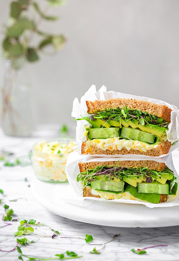 egg and avocado salad sandwich with microherbs on a marble plate
