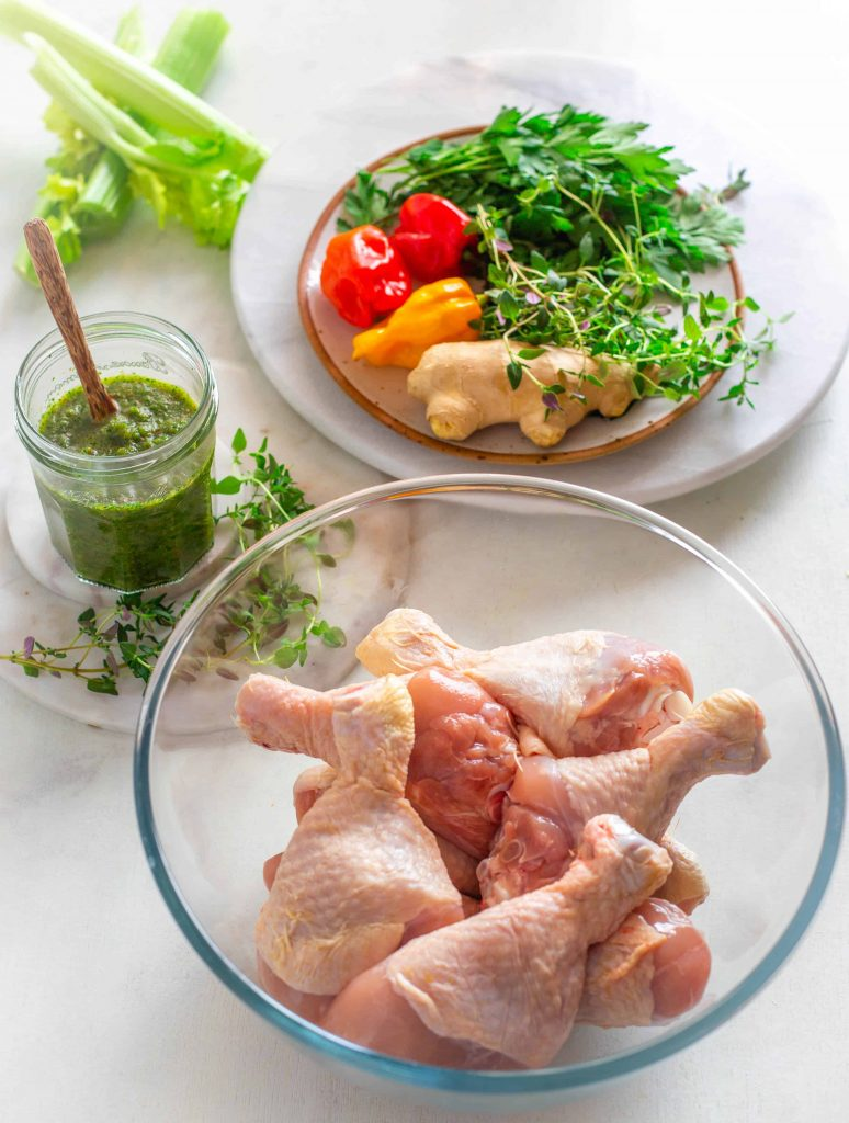 raw chicken and a jar of caribbean green seasoning