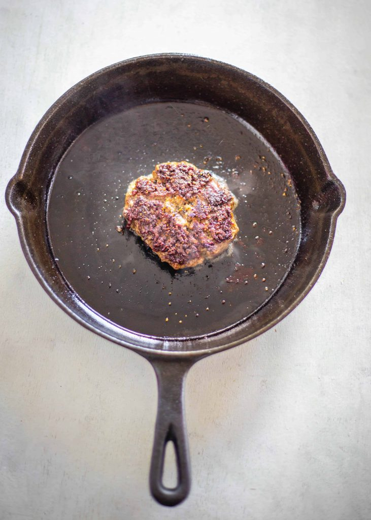 beef burger patty cooking in the cast iron skillet
