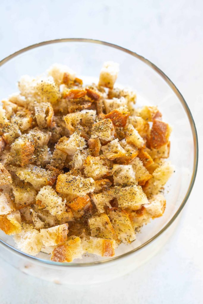 uncooked croutons in a bowl seasoned