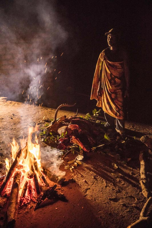 A man from a local village preparing bushmeat (poached antelope) on a fire outside his home. Preparing bushmeat right after a kill is essential to ensure that the meat is safe to eat. An antelope can feed a family for weeks and all parts of the animal will be used by the family.