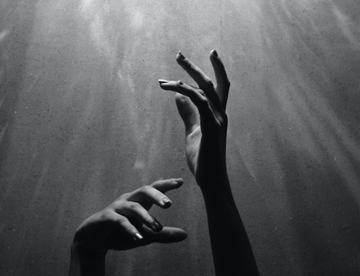 a black and white photo of hands reaching up towards a light