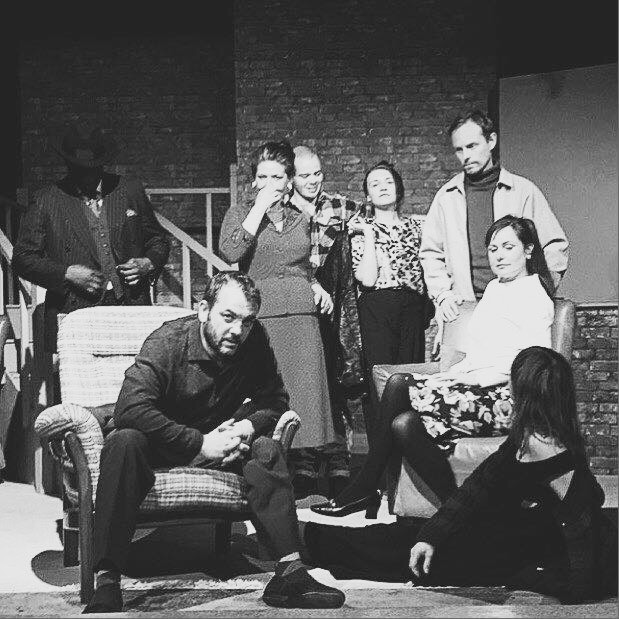 Production shot from a play showing a group of actors in costume