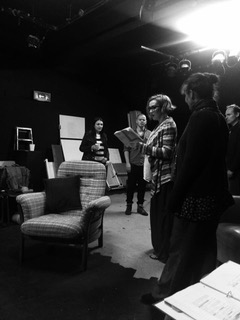 Director with script speaks to actors in a rehearsal