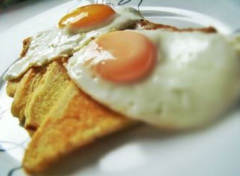 Steam-fried eggs over easy, over olive oil fried bread