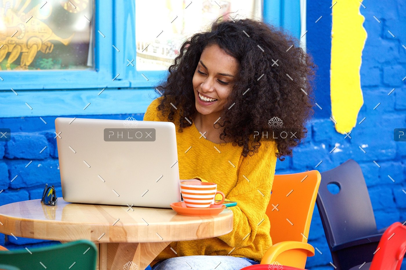 demo-attachment-65-happy-young-woman-sitting-at-outdoor-cafe-using-PFFBJ93