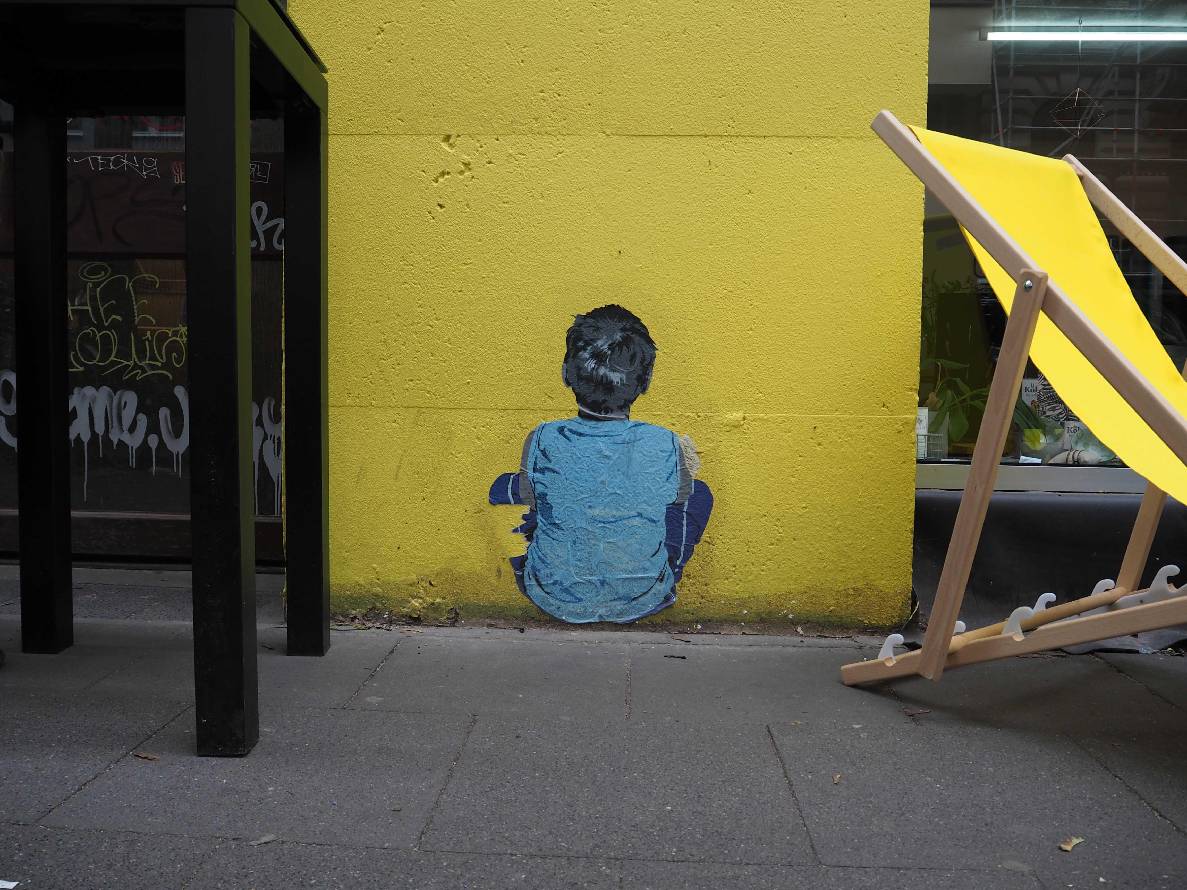 ein Junge sitzt von hinten dargestellt auf einer gelben Wand, Bild von Lei Leise