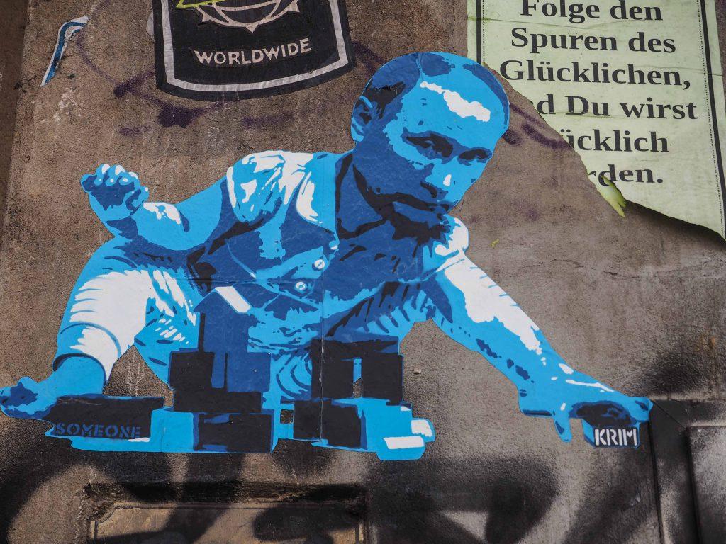 Someone klebte Putin der mit Bauklötzen spielt an die Wand