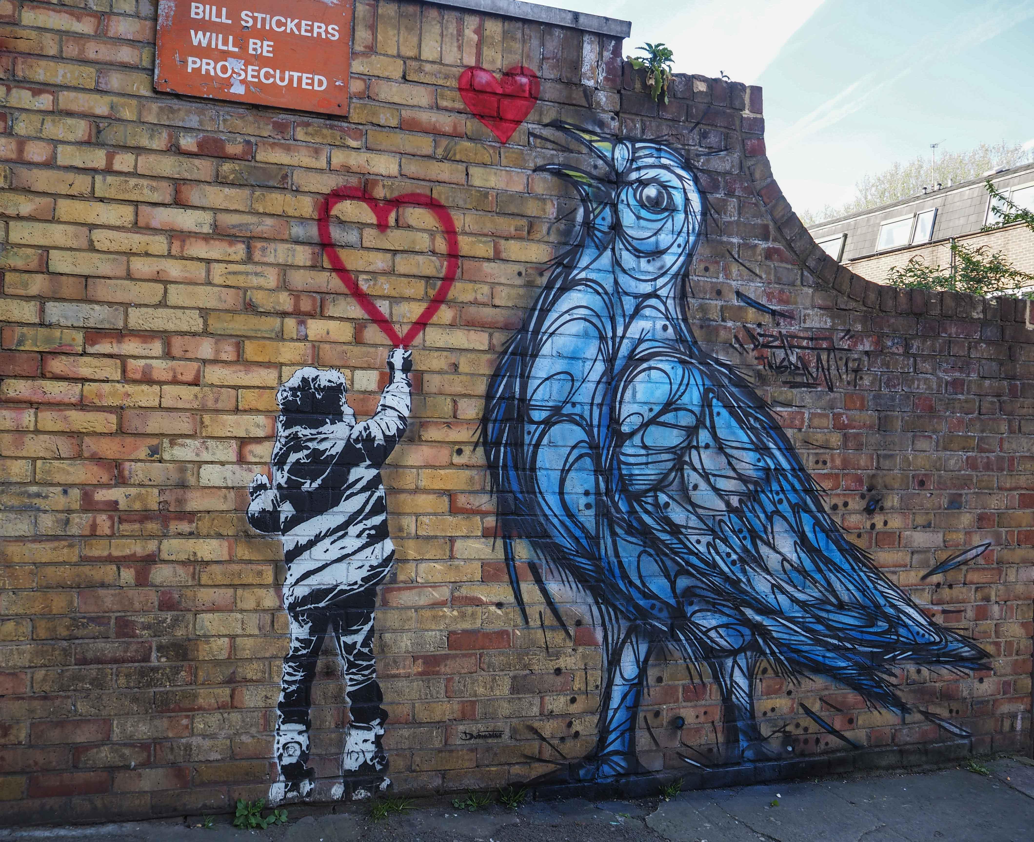 Mural von Dzia zeigt einen großen Vogel und einen Jungen der ein Herz malt