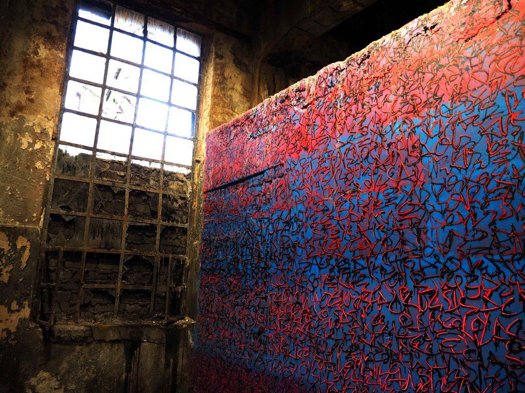 Detail von der Arbeit von Tanc auf dem eine getaggte Wand und ein Fenster zu sehen sind.