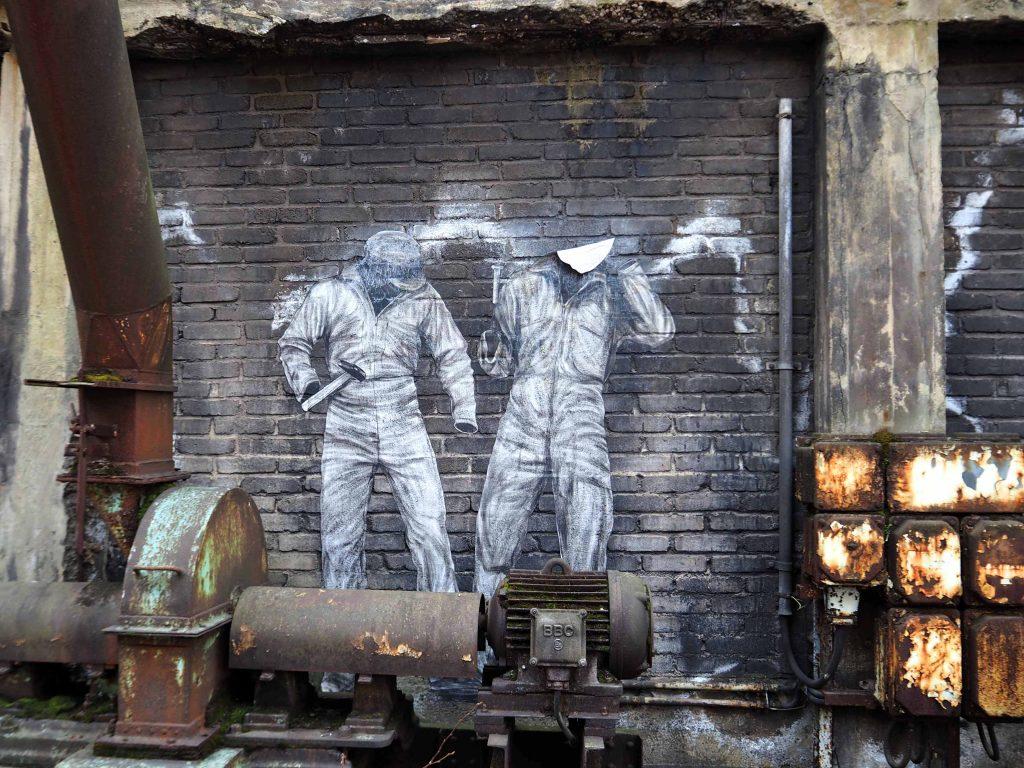 Zwei Arbeiter ohne Körper, nur mit Kleidung und Werkzeug von Levalet
