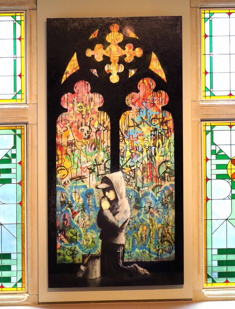 Junge betet vor Kirchenfenster