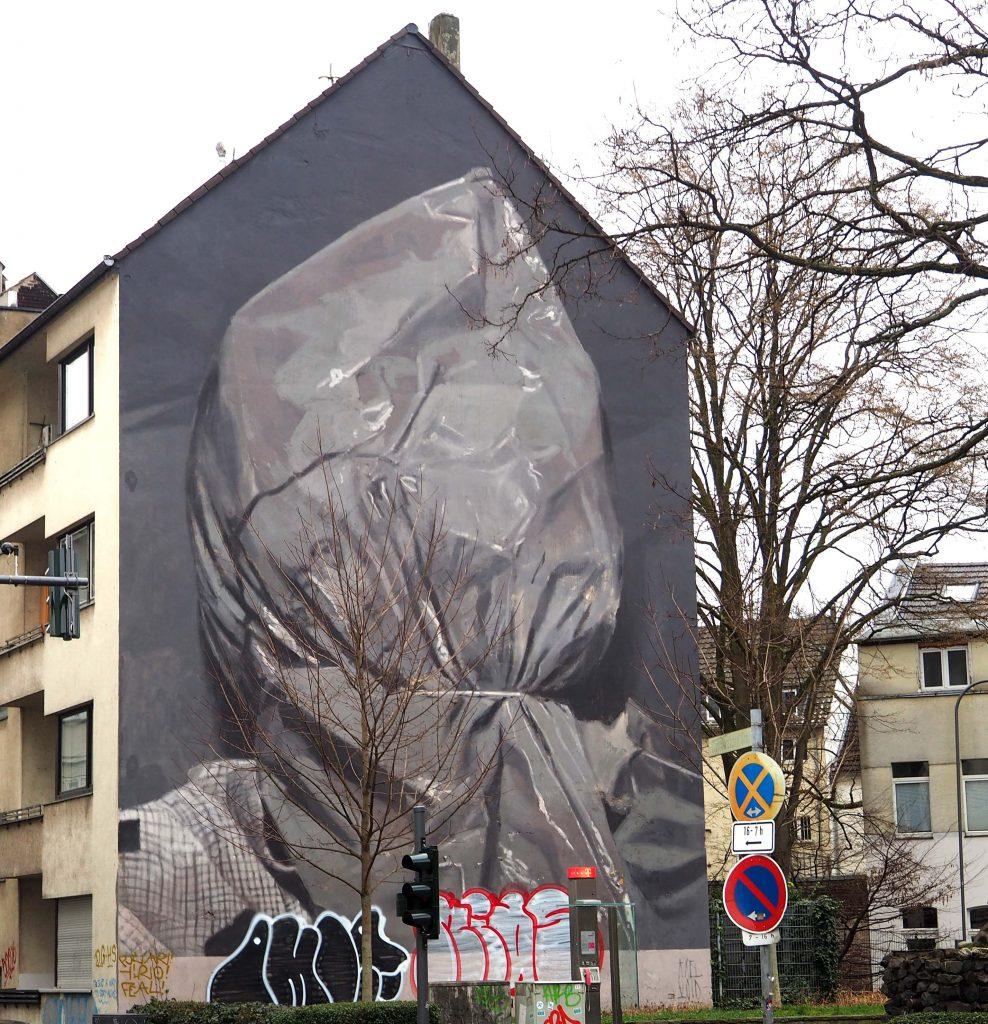Mensch mit Plastiktüte über dem Kopf