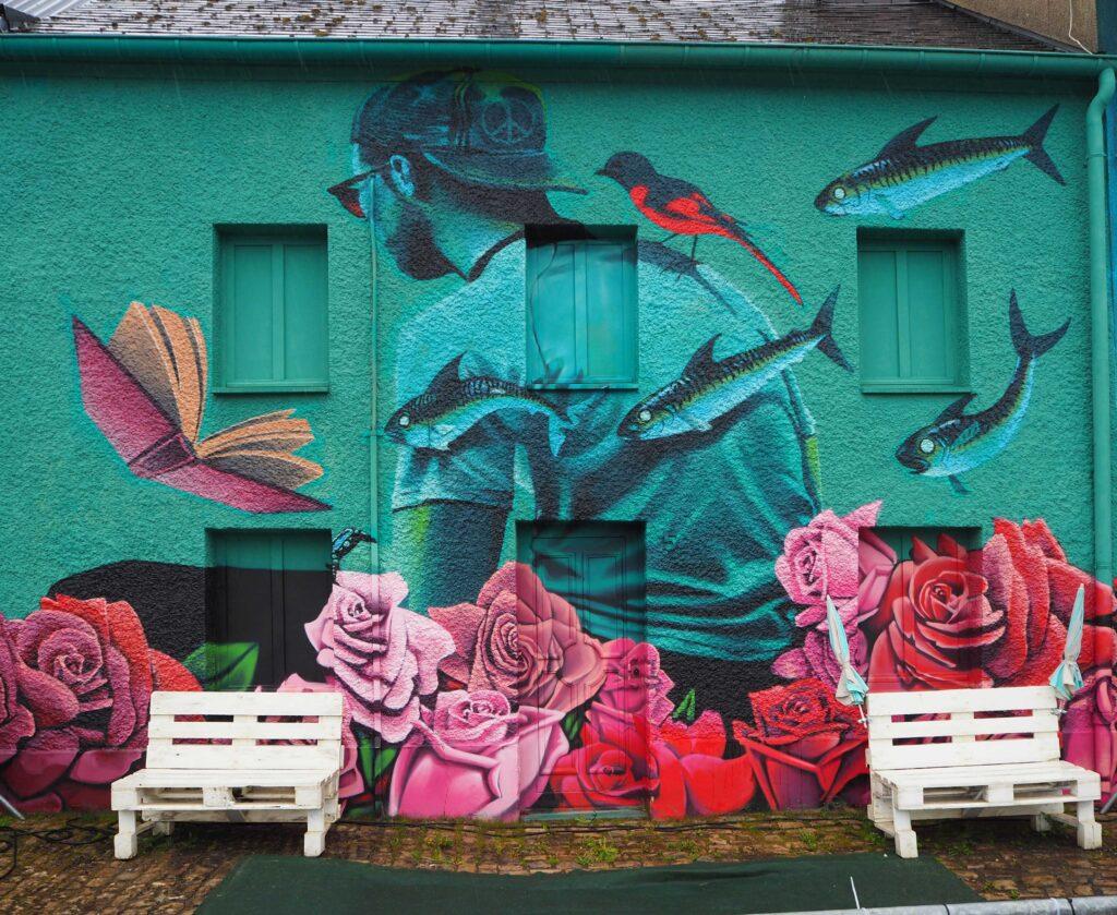 Mann hinter Rosen mit Fischen, Buch und Vogel