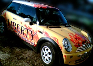 Vehicle wrap sign stickers, for Liberty Estate agents with flames on the mini. Call us today for a competitive quote to design, make and Install frosted vinyl, tinted window film, cut vinyl sign stickers and digital printed vinyl.