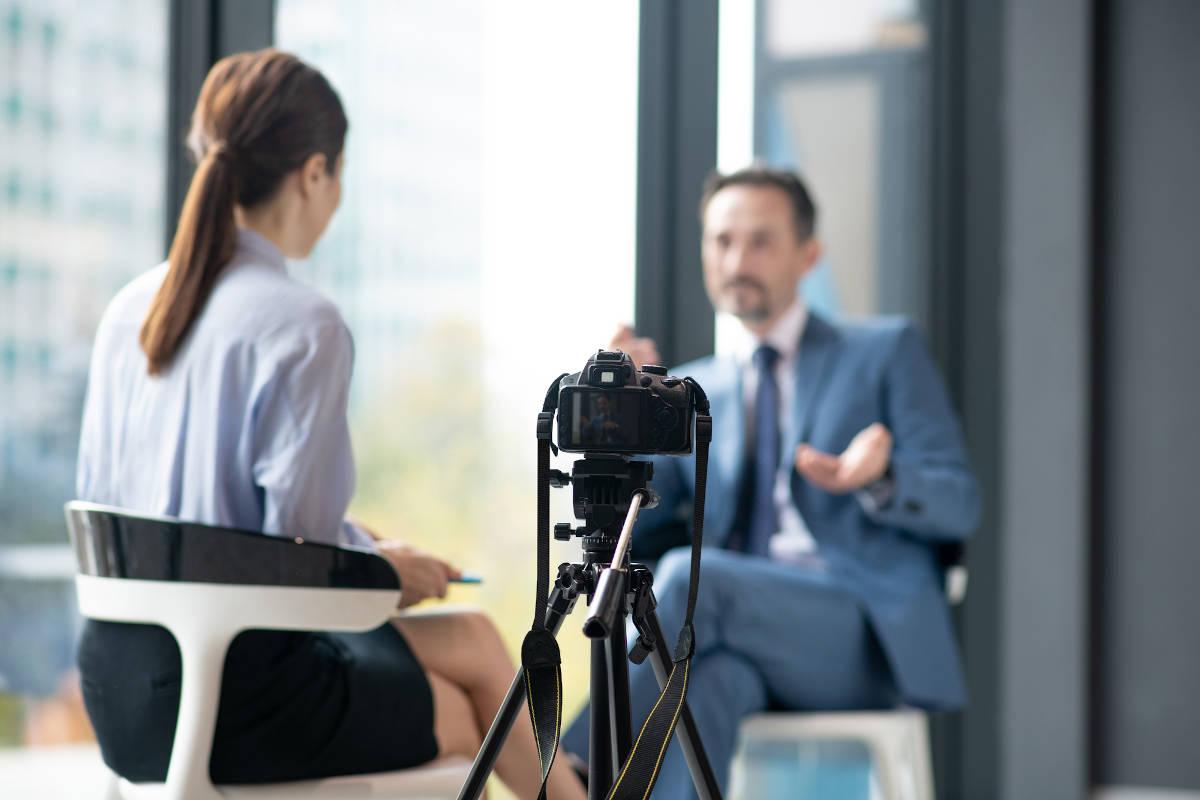 Frau interviewt mann mit Videokamera