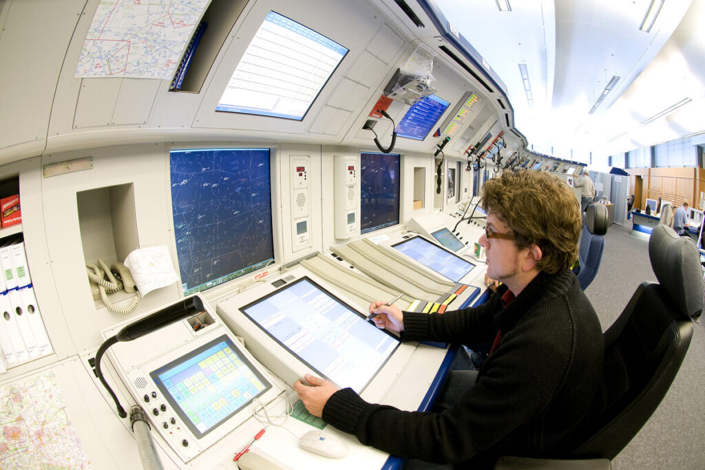 Männlicher Fluglotse sitzt an Kontrollplatz vor Radardisplay