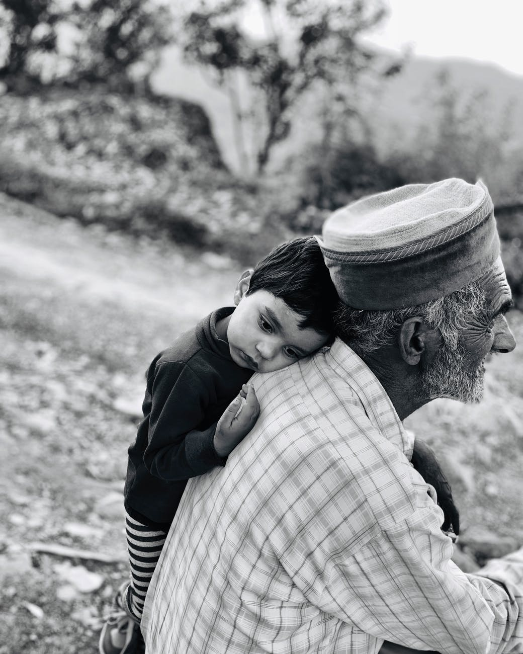 boy leaning beside an old man