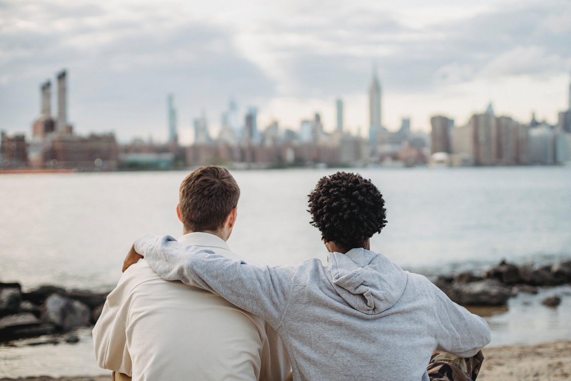 diverse best friends hugging on embankment