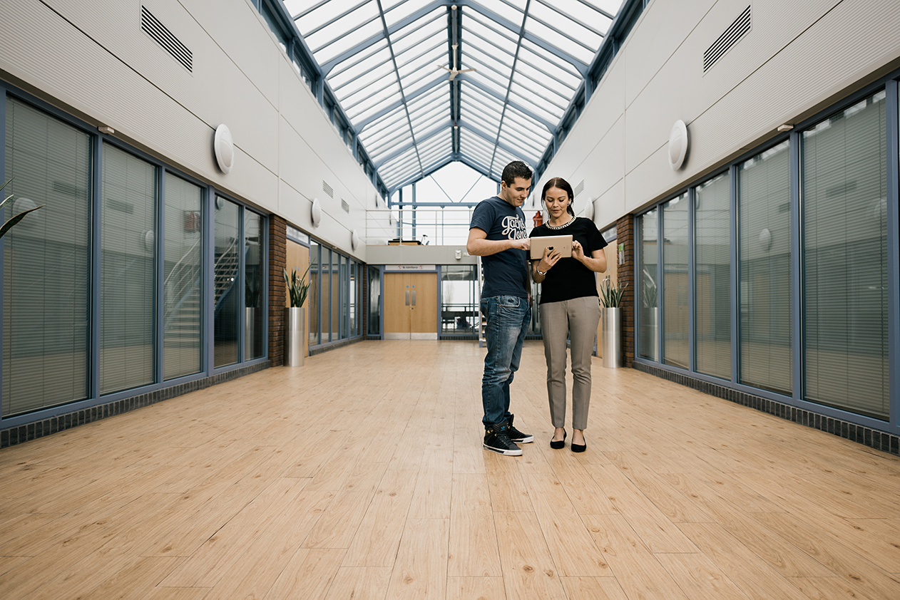 Two coworkers stand in lobby of the Arden Software building