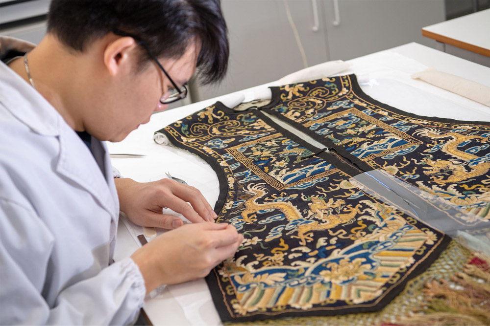 Centre for Textile Conservation - MPhil student supporting the highly embroidered panels from an 18th century waistcoat