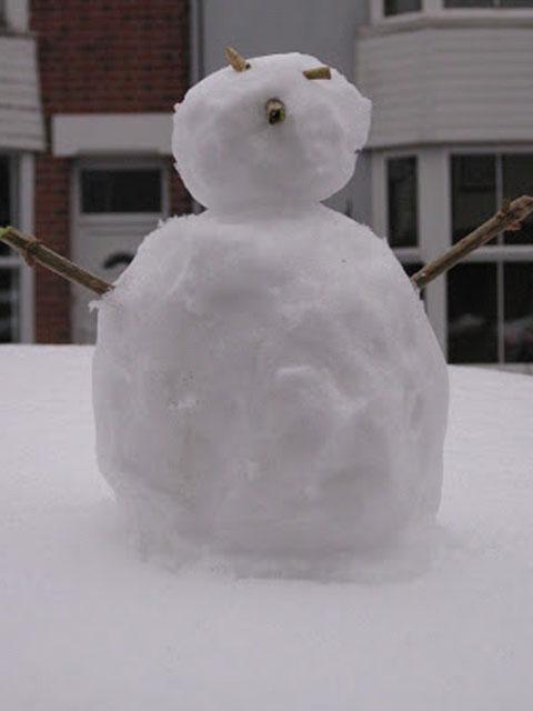 A small snowman sitting on a car