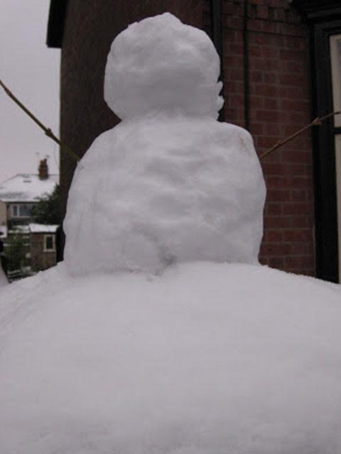 A small snowman sitting on a snowy pillar