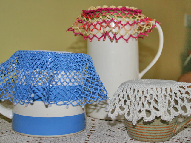 Three crocheted milk jug covers