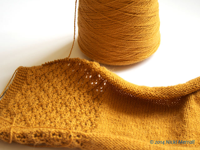 Cone of mustard-coloured Angora yarn with hand-knitted lace swatch made from yarn
