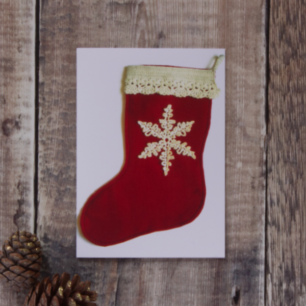 Photo of a greetings card on a wooden background. Greetings card shows a red felt Christmas stocking with cream crochet trim