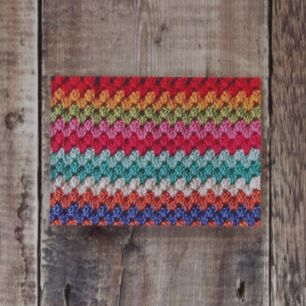 Photo of Granny Stripes greetings card on wooden background. Greetings card shows detail of some colourful crochet worked in granny stripes