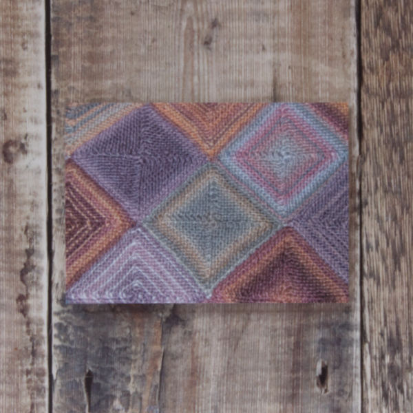 Photo of Kairouan greetings card on wooden background. Greetings card shows detail of hand-knit throw worked in mitred squares using variegated yarns
