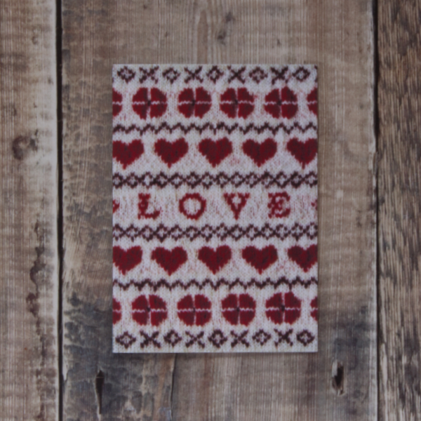 Photo of Love and Hearts greetings card on wooden background. Greetings card shows Fair Isle design featuring hearts, flowers and the word love