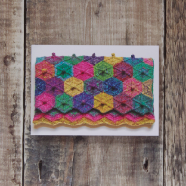 Photo of Magic of the Circus greetings card on wooden background. Greetings card shows knitted clutch bag: flap features mitred hexagons and main bag has chevrons