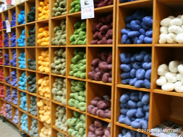 Shelves holding woollen yarn arranged by colour and value