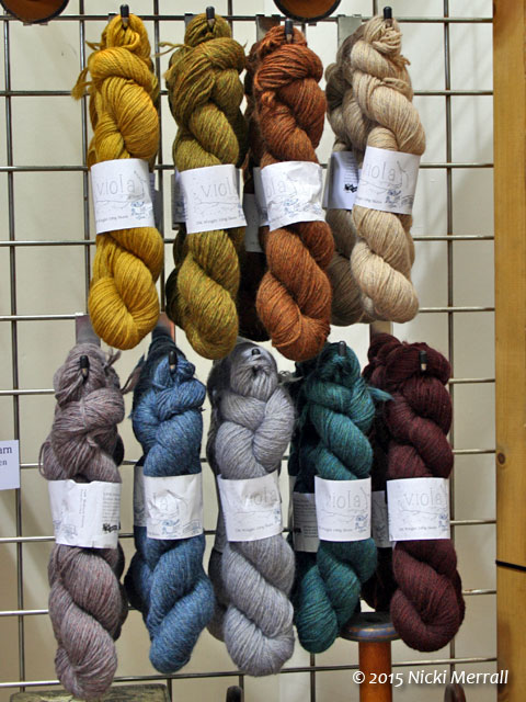 Hanks of yarn in muted colours hanging on grid wall