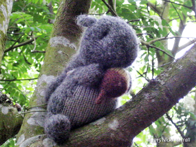 Knitted squirrel holding a knitted nut sitting on real branch