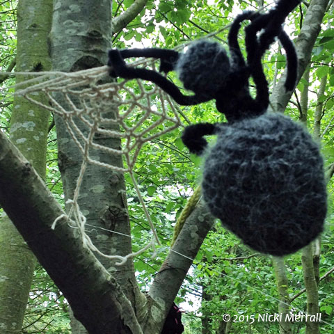 Knitted spider and web in a tree