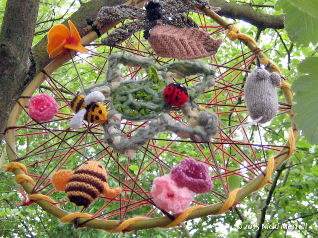 Several knitted creatures and flowers suspended in a tree