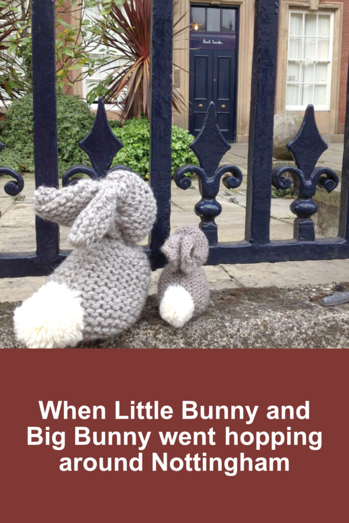 Little Bunny and Big Bunny looking through black railings at Paul Smith shop in Nottingham