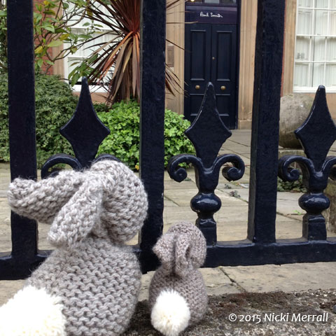 Little Bunny and Big Bunny looking through the railings at Paul Smith's shop