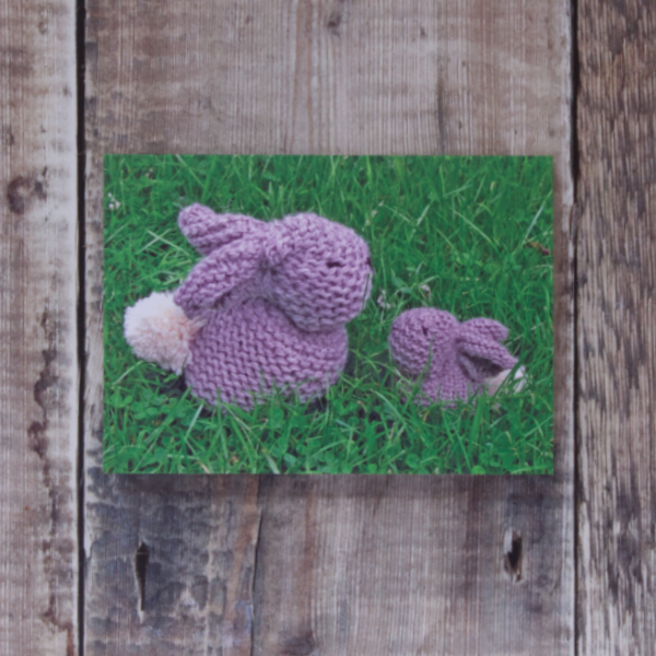 Photo of Bunnies greetings card on wooden background. Greetings card shows two small grey knitted bunnies sitting on grass
