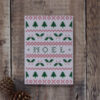 Photo of Noel greetings card on wooden background. Greetings card shows chart for Fair Isle or cross stitch design featuring fir trees, holly and the word Noel