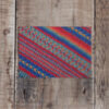 Photo of Painterly greetings card on wooden background. Greetings card shows stitch detail of Painterly, hand-knit shawl