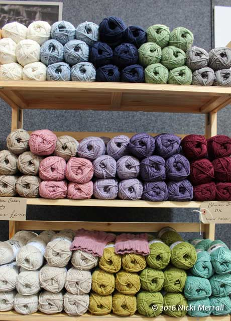 Wooden shelves holding balls of wool arranged by colour